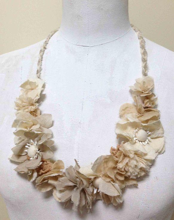 ベージュの花のネックレスです。紅茶染めしたいろいろな種類のコットン生地やグレーぽいベージュが美しいシルクでひとつひとつ小花を作り、ちくちく留め付けてネックレス...|ハンドメイド、手作り、手仕事品の通販・販売・購入ならCreema。
