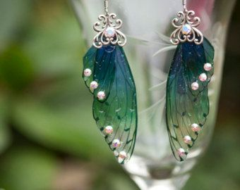 The Spriggan Fairy Wing earrings are made with our green and blue toned special ombre mini fairy wings and accented with Swarovski rhinestones and a filigree brass stamping. The ear wires are 18 kt gold plated  These earrings are so stunning in person, we combined our love art nouveau and fairy magic to create this unique pair of earrings.  No Fairies were harmed in the making of this jewelry.  We ship rush and internationally. Send us a message to inquire about prices. We also make these in…