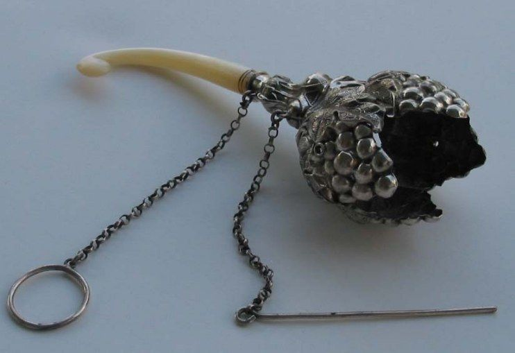 Posy holder with an ivory handle and a finger ring - meant to be carried in the hand at a ball.  The pin skewers the posy into place.   The posy would swing freely from the lady's hand as she danced.