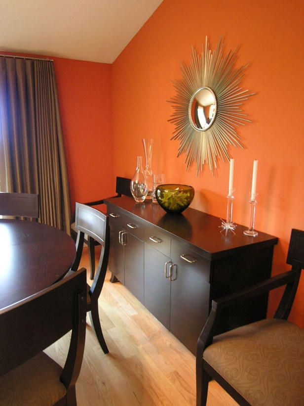 Vibrant Dining The Dark Wood Set And Buffet Are A Sweet Complement To Pumpkin Orange Walls In This Chic Room Gold Sunburst Mirror Echoes