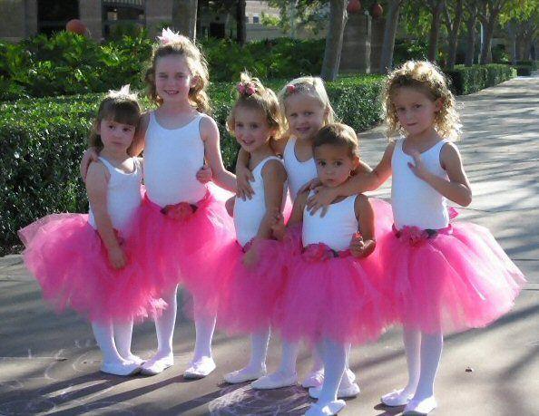 29bcb969c Flower girls wearing hot pink poofy peony tutus as flower girl dresses.  Each tutu is