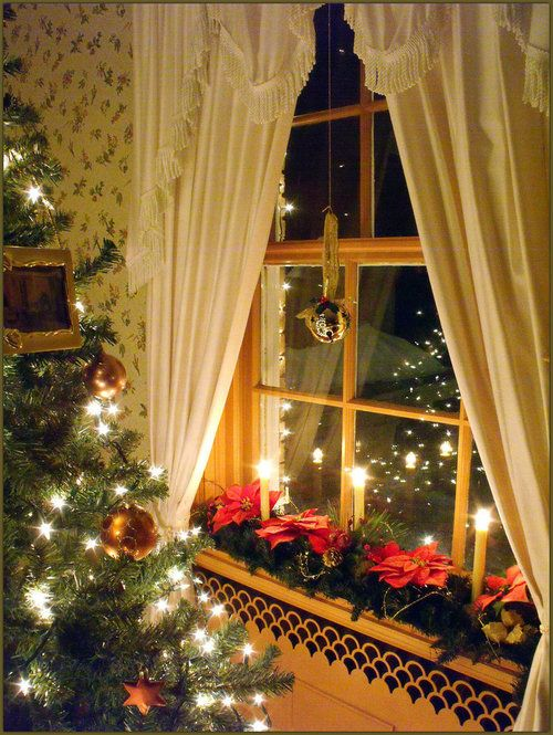 christmas decor along window sill and a single ornament hanging in window could keep curtains up