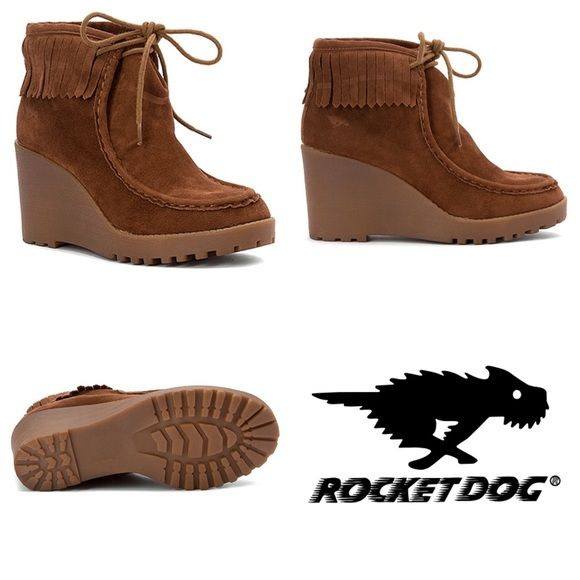 """Rocket Dog Sandie Wedge Booties New, never worn! Retail $80. A perky combination of desert boot and moccasin, the Rocket Dog Sandie wedge bootie features a faux suede upper with a neat row of fringe trim and rustic moc-toe stitching. The durable synthetic outsole is lightly treaded for versatile and reliable traction. Features: lace-up design, round, moc toe, synthetic outsole, faux suede upper, heal height - 3"""". Platform Height 1"""". Shaft 4.5"""". Textile lining and footbed. Rocket Dog Shoes…"""