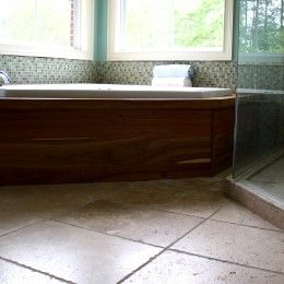 Travertine tile with frameless glass enclosure and custom