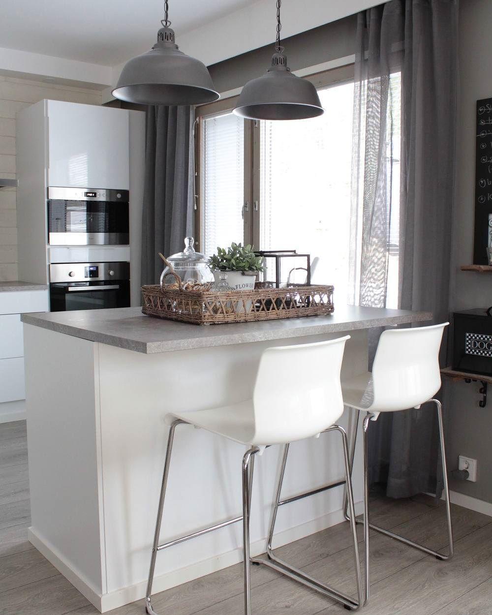 Riippuvalaisimet keittiösaarekkeen yläpuolella rytmittävät kivasti tilaa.