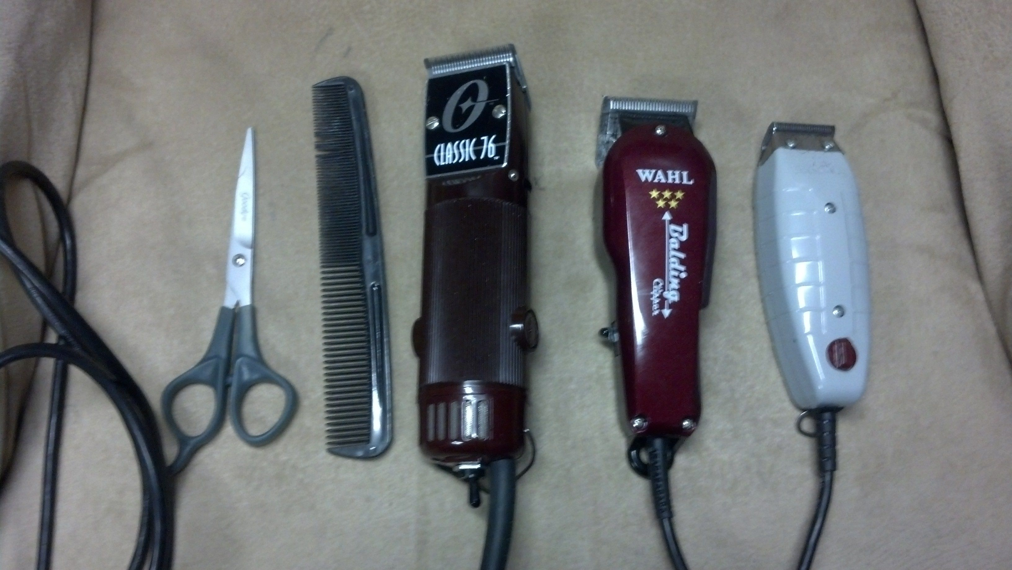 My beloved clippers. In the middle, the big, bad Oster 76s. To its right, the Wahl 5 Star Balding Clippers, and the to the far right the Andis Outliners. Need a haircut?  Yeah, yeah, I need a new comb and better scissors, but I needed something to balance them out.