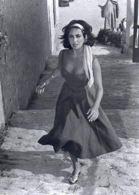 """1959 USA. Film: Set of Suddenly last Summer. SPAIN. Sagaro. 1959. Twenty-five-year-old Elizabeth TAYLOR ignores the begging of beach urchins in a scene from """"Suddenly Last Summer"""", in which she co-stars with Katharine Hepburn and Montgomery Clift. I"""