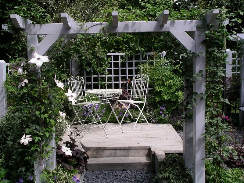 Softwood decked area under a pergola painted in soft grey for Garden decking colours