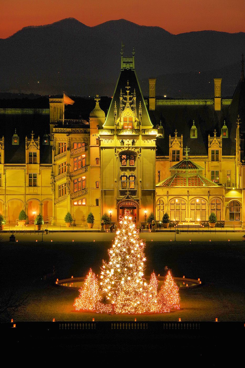 Biltmore House with giant Christmas Tree with sunset over the Blue ...