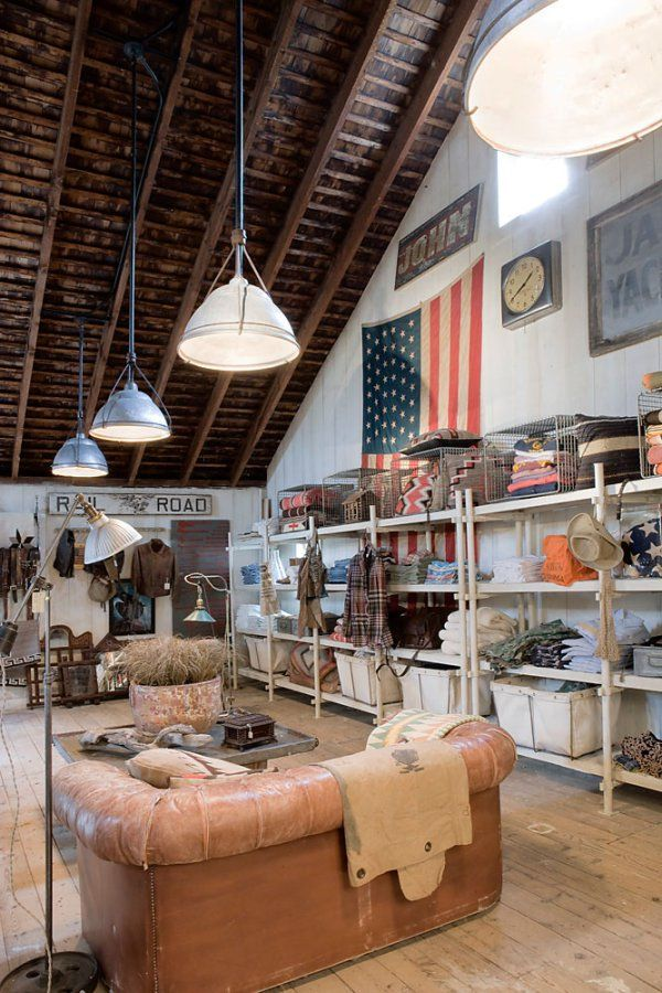 Love the dark natural ceiling with the white washed walls. The shelving is cool with the old canvas totes too.
