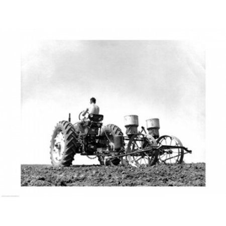 Low angle view of a farmer planting corn with a tractor in a field Canvas Art - (18 x 24)
