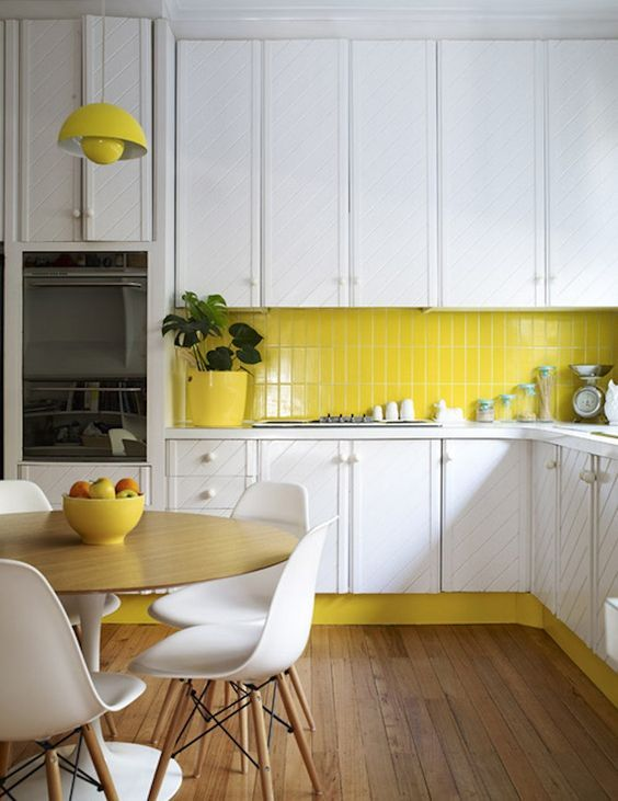 a white kitchen is enlivened with a neon yellow tile backsplash ...