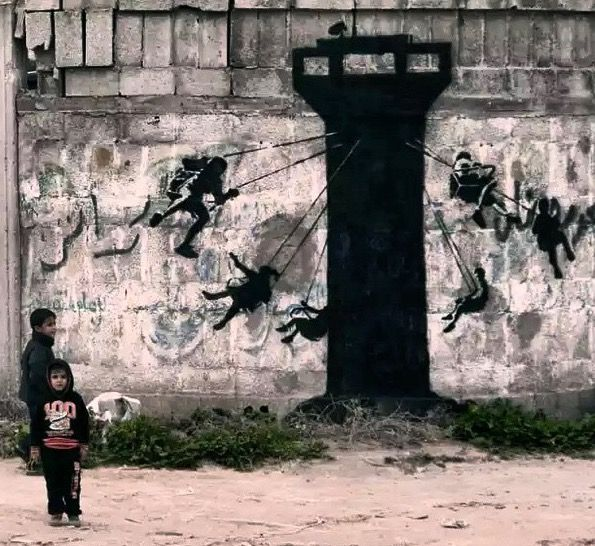 "Street art | Mural ""Chair swing ride [children riding a chair swing ride that is circling around a looming guard stations]"" (Gaza, Palestine, Feb15) by Banksy"