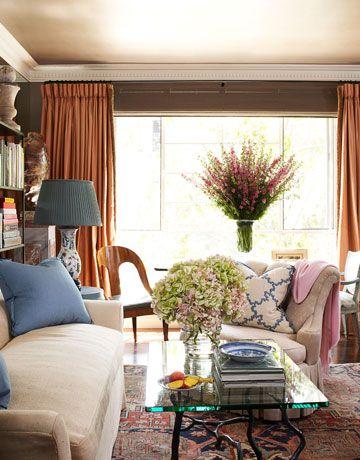Light-flooded living room - traditional rug, neutral sofa, blue pillows, pink throw, glass table, hydrangeas - Joe Nye