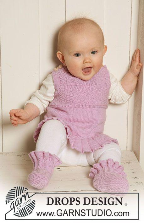 """Sættet består af: DROPS kjole / vest med flæse og strukturmønster og tøfler med flæser i """"Baby Merino"""". ~ DROPS Design"""