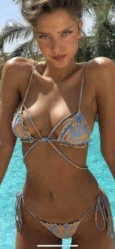 e970160874243 Seductive looking perky boobed woman in the swimming pool in hot bikini  swimwear.