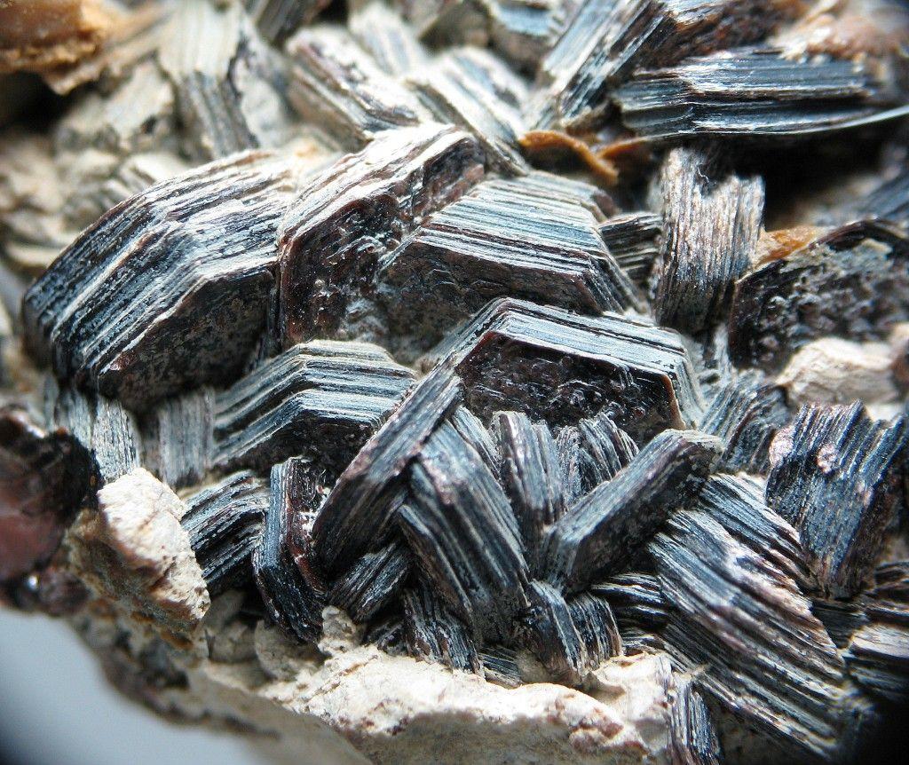 Biotite (Var: Manganophyllite) K(Mn,Mg,Al)2-3(Al,Si)4O10(OH)2, Harstigen Mine, Pajsberg, Persberg district, Filipstad, Värmland, Sweden. Fov 2 cm. Platy, hexagonal crystals associated with many unidentified minerals. Copyright: © Christopher O'Neill