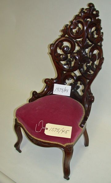 """This parlor chair, once owned by Josefita Manderfield, came to Santa Fe from Durango, Mexico, by ox cart. Made of mahogany-stained hardwood, its back two pieces are a highly carved """"Belter type."""" This is among the many items in the New Mexico History Museum's Manderfield Territorial Collection, which contains items dating back to the early 1800s."""