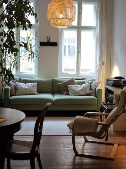 Wohnzimmer mit Couch in schönem Mintgrün und moderner Lampe