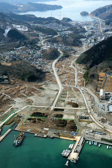"""THEN AND NOW: Photos compare changes in disaster zone--- NOW: Onagawa, Miyagi Prefecture, pictured on Feb. 14, 2013. The passenger ship terminal has been dismantled and only piles of soil remain where it once stood. The words """"We (love) Onagawa"""" have appeared in fields to the right. (Shiro Nishihata)"""