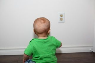 a baby sitting and looking at a power outlet