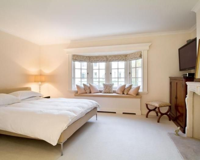 Photo Of Neutral Beige White Dark Wood Bedroom With Bay Window Fireplace Window Window Seat And