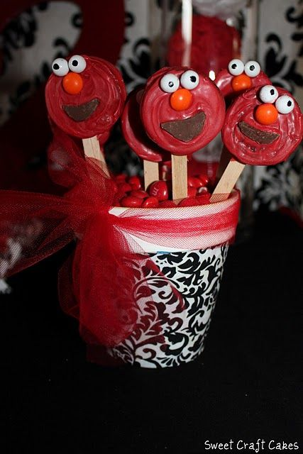 chocolate covered Oreo Elmo pops.  She dipped the Oreos into candy melts, added sixlets for his eyes,  an orange skittle for his nose, and then cut a chocolate candy melt for his mouth