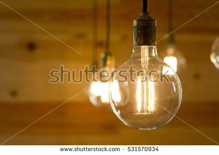 Closeup image of a filament light bulb turned on, over a wooden background.