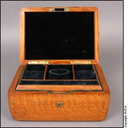 A vintage wooden jewelry box with inset and velvet lining