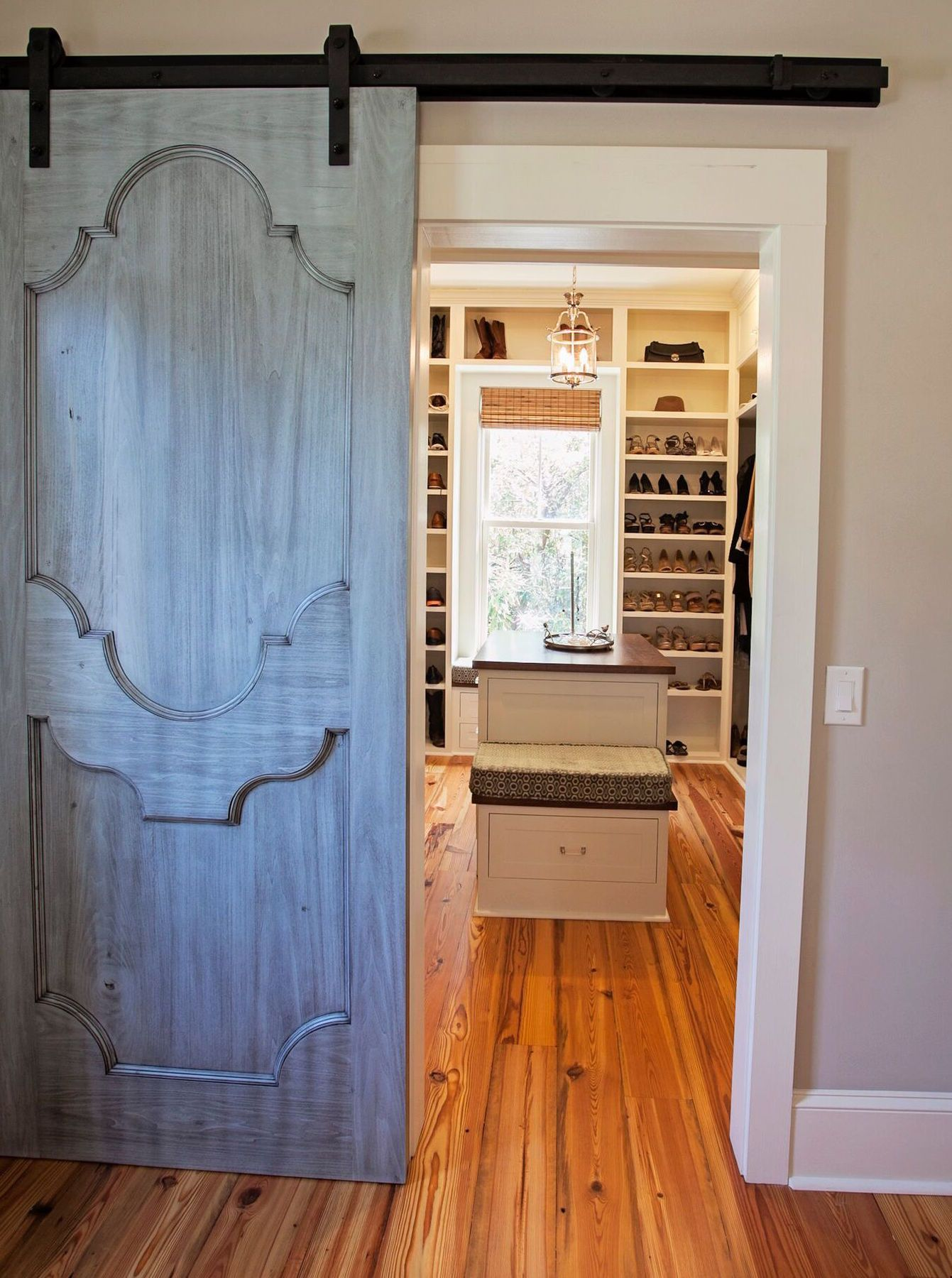 A barn door with an aged blue patina separates the master bedroom from the swanky closet