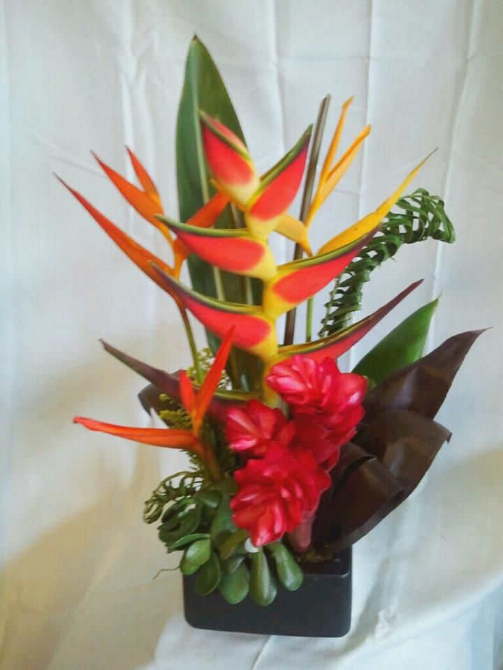 Lobster claw heliconia, ginger flowers, heliconias, jade plant, braided palm, and ti leaves.