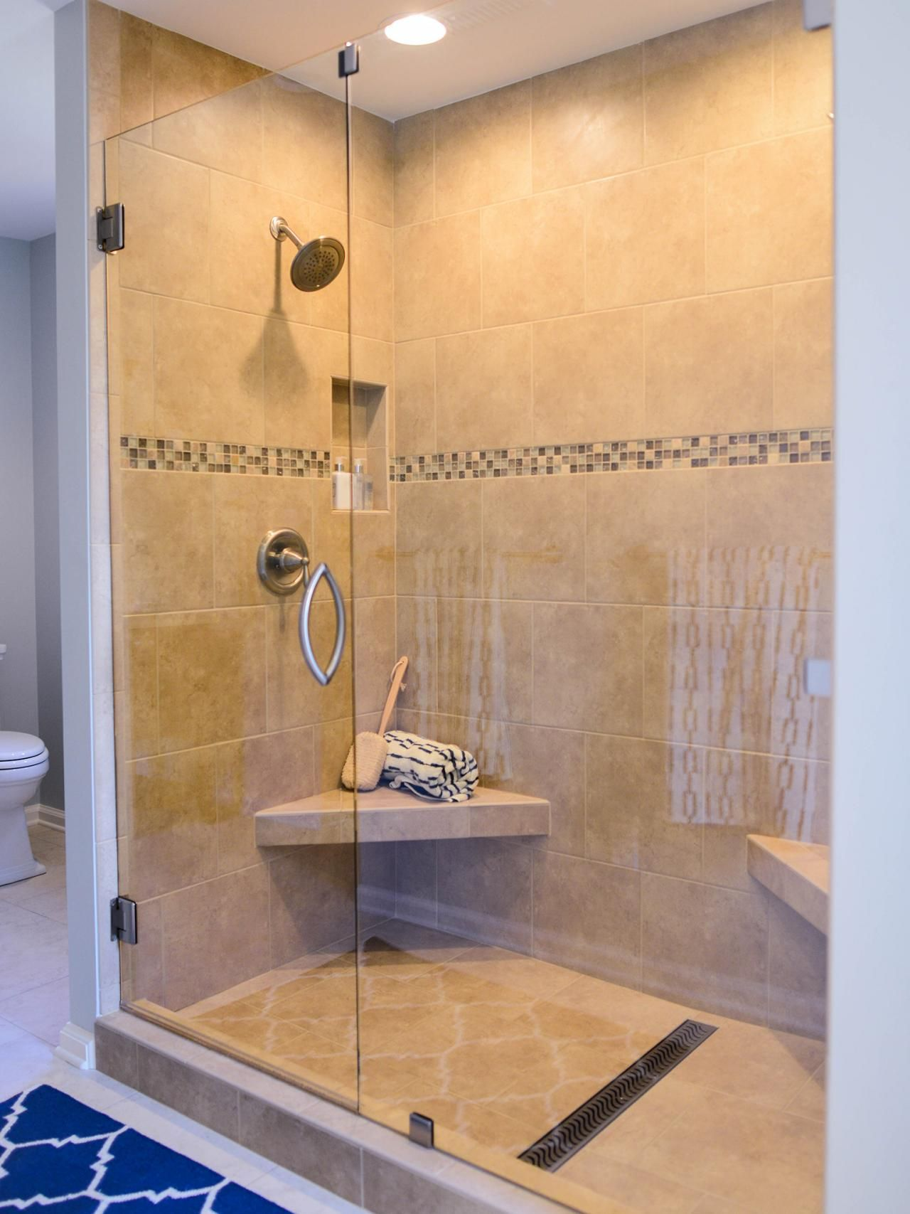 This custom tile shower has two shower heads and corner seats to ...