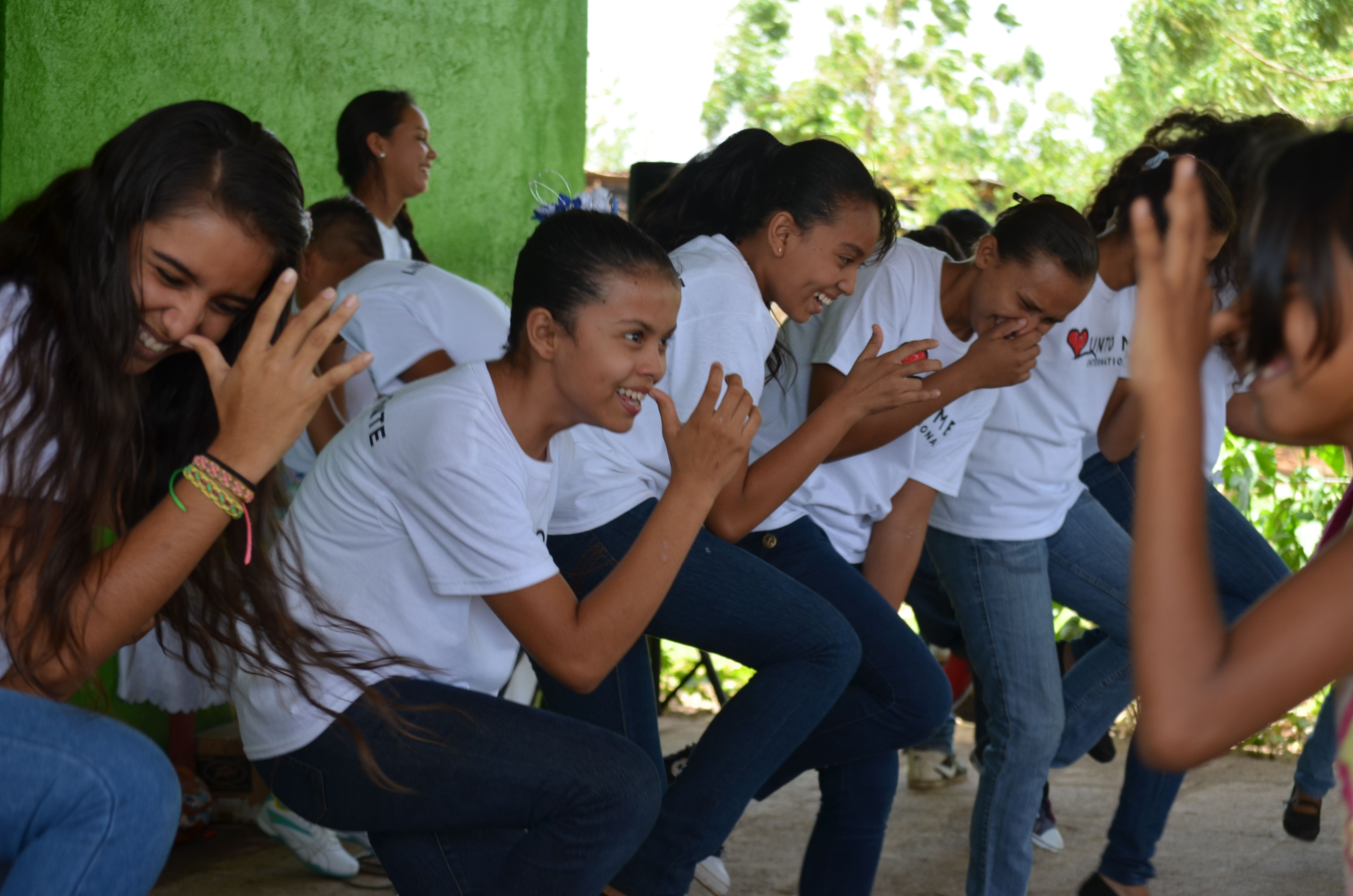 Teen leadership teaching the children a song and dance.