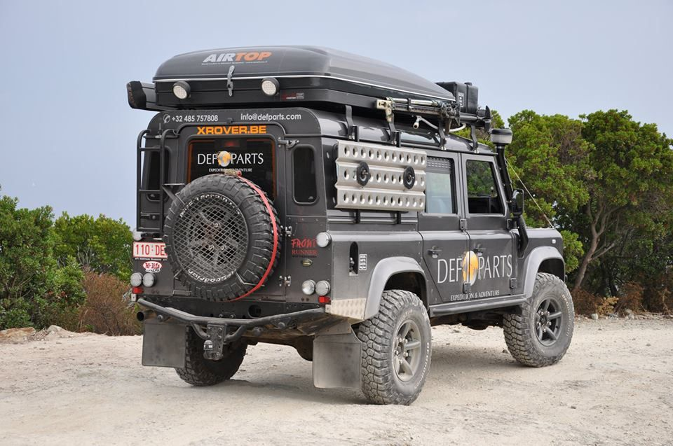 Rover outfitted. BBQ grill on back spare. Hard top tent when folded is low profile, sand ladders act as a window protector, two rear work lights, awning on the port side.