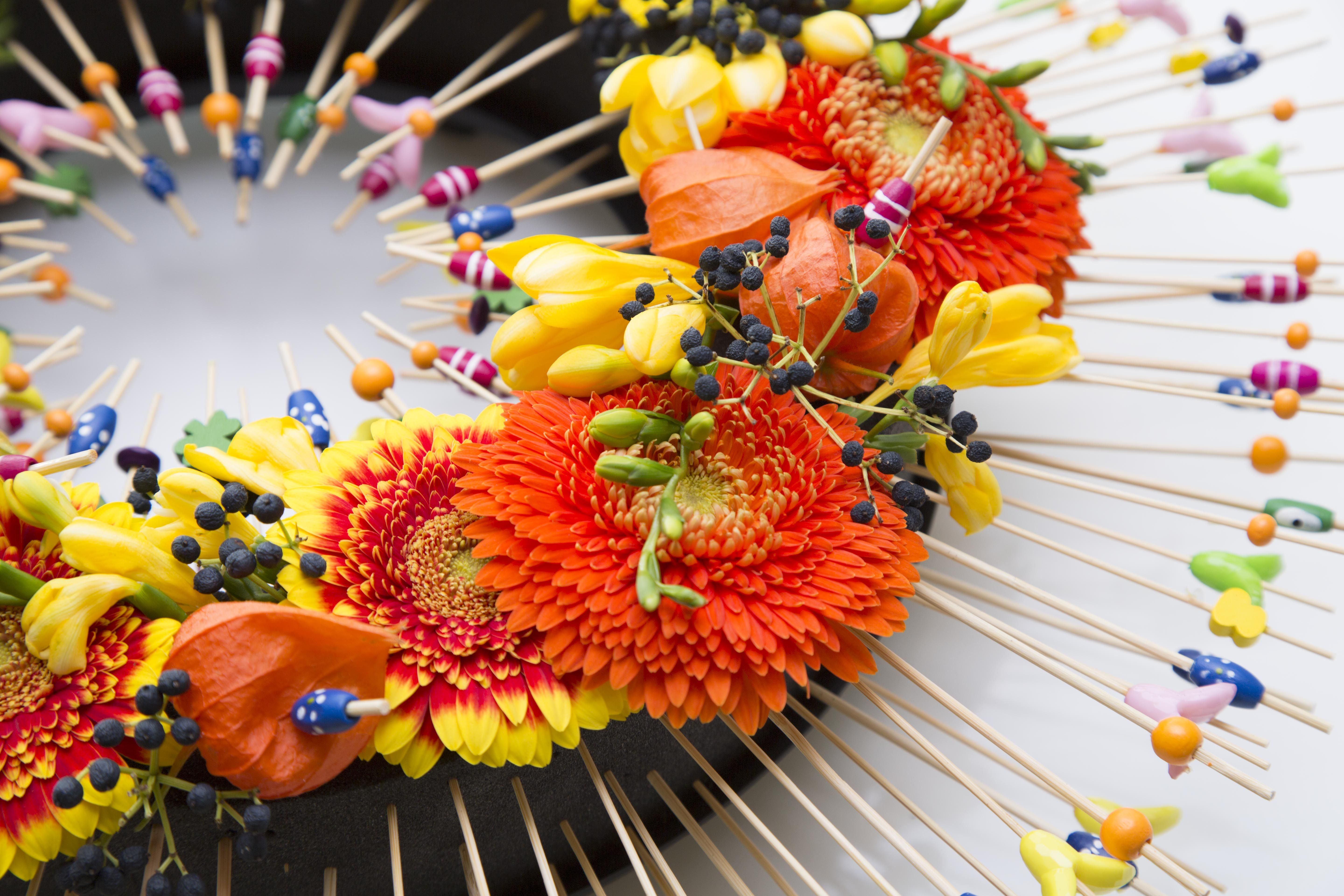 Colors that pop, that's what Alex Segura likes in his floral design. In this flower arrangement he used 'Eychenne All Black' foam by Oasis, which makes an even sharper contrast with the bright colored gerberas 'Anita' and 'Antique', freesia 'Soleil', Physalis and Viburnum. Fun cocktail sticks add to a summery feeling!
