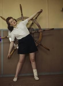 """A REHABILITATION CENTRE FOR INJURED WORKERS AT A FACTORY IN BRITAIN, 1944  part of """"MINISTRY OF INFORMATION SECOND WORLD WAR COLOUR TRANSPARENCY COLLECTION"""" (photographs) Made by: Ministry of Information official photographer  TR 1729  A girl using a nautical wheel for resisted trunk side flexion exercises at a rehabilitation centre for injured workers. The centre was run by a large glass factory in the north of England."""