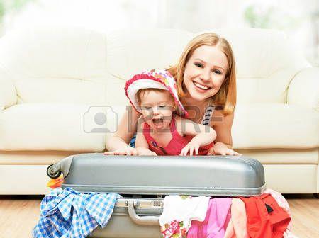 Madre y bebé con la maleta de equipaje y ropa lista para viajar en vacaciones.