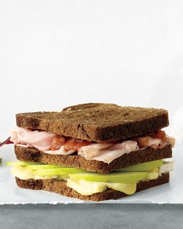 Ham, Brie, and Apple Triple-Decker Sandwich - Delight your senses with the interplay of salty, sweet, and rich flavors, along with crunchy and creamy textures, in this out-of-the-ordinary ham and cheese sandwich. In place of pumpernickel, you could also use toasted sourdough or whole-grain bread.