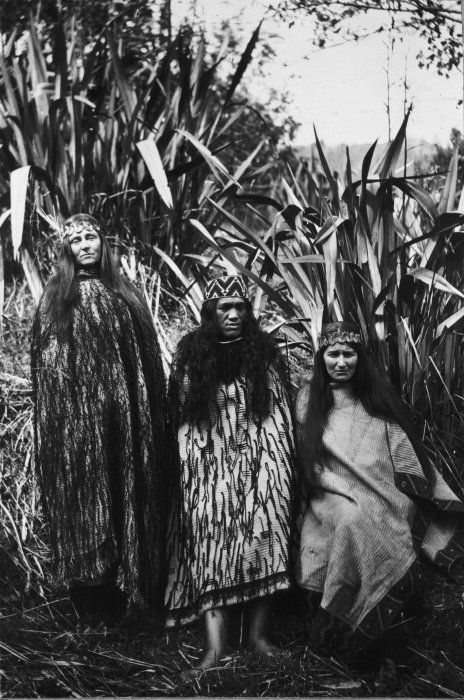 Three women wearing cloaks, 1921  Three  Koroniti women model fine flax cloaks.  Two are decorated with short  black cords (cloaks decorated in this way are called korowai).  One is  decorated with taniko boarders (cloaks decorated in this way are called  kaitaka).  Photographed by James Ingram McDonald in 1921