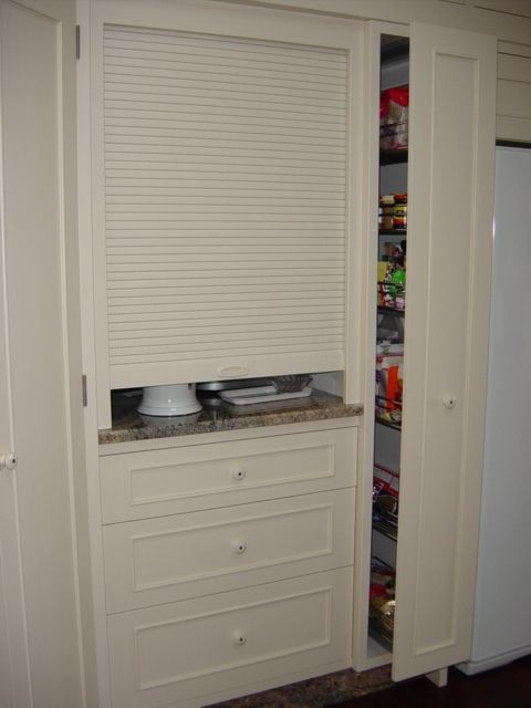 roller door and pull-out pantry hide kitchen appliances and food ...