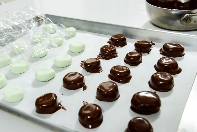 Coat each peppermint patty in melted chocolate.