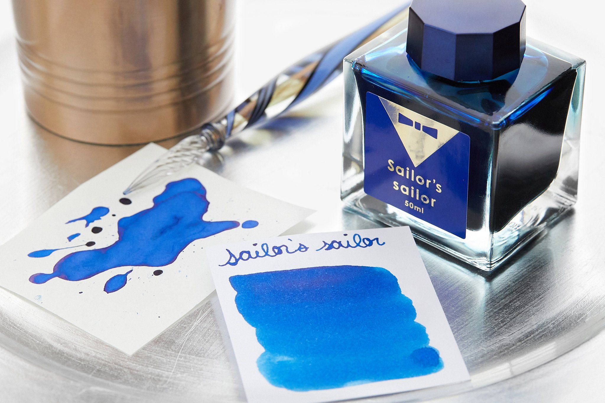50ml square glass bottle of Sailor's sailor special edition Ocean Blue fountain pen ink. It is set in a special box along with an anniversary card and ink leaflet. For the past 15 years, Sailor has been actively holding Ink Studio in-shop ink blending events all throughout Japan. These sought after events have always been a success with Japanese consumers lining up to have custom ink colors blended by their famed Sailor ink blender Osamu Ishimaru. At the event, the blender wears a barman's unifo