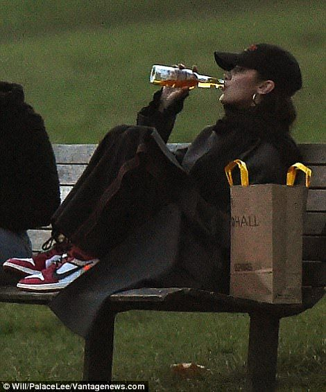 Bella Hadid chugs cider from the bottle on a park