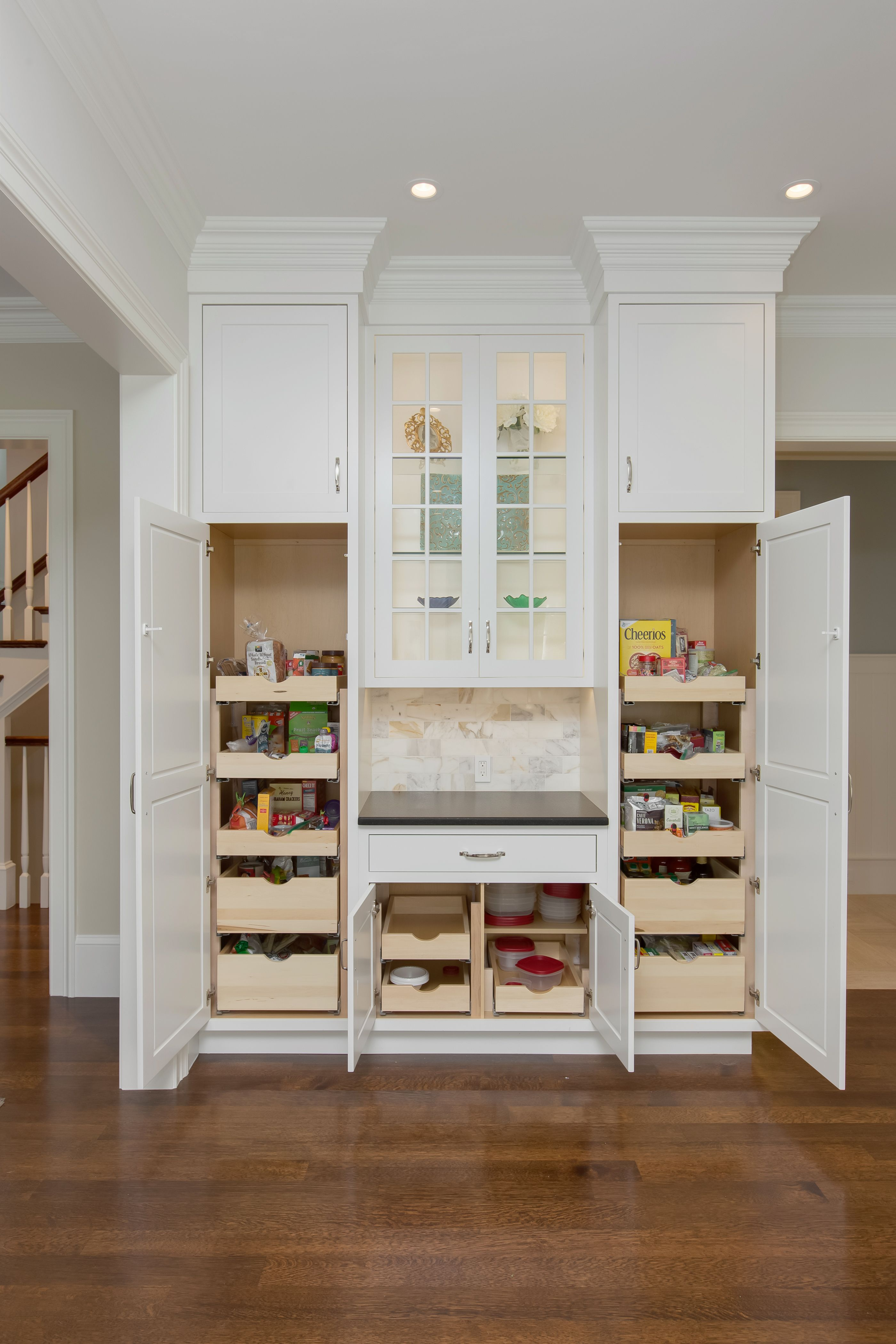 pantry with pull out drawers and crown molding in