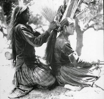 Photo of Navajo (Diné) mother tying her daughter's hair using brush. Undated (1920s?). S…
