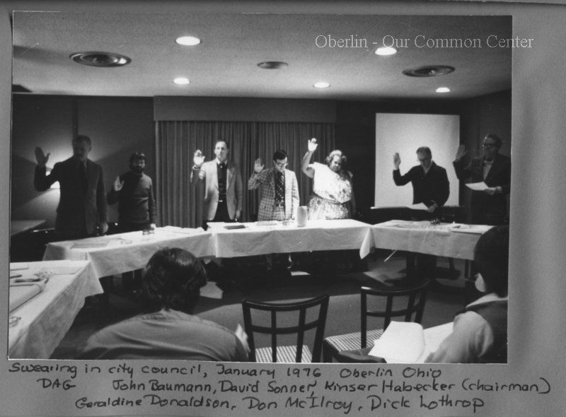 ID#0505 Date: 1976. This image shows the city council being sworn into office, January 1976. From left to right: Dewey Ganzel, John Baumann, David Sonner, Kinser Habecker (chairman) Geraldine Donaldson, Don McIlroy, Dick Lothrop. Participants: Carol and Dewey Ganzel.