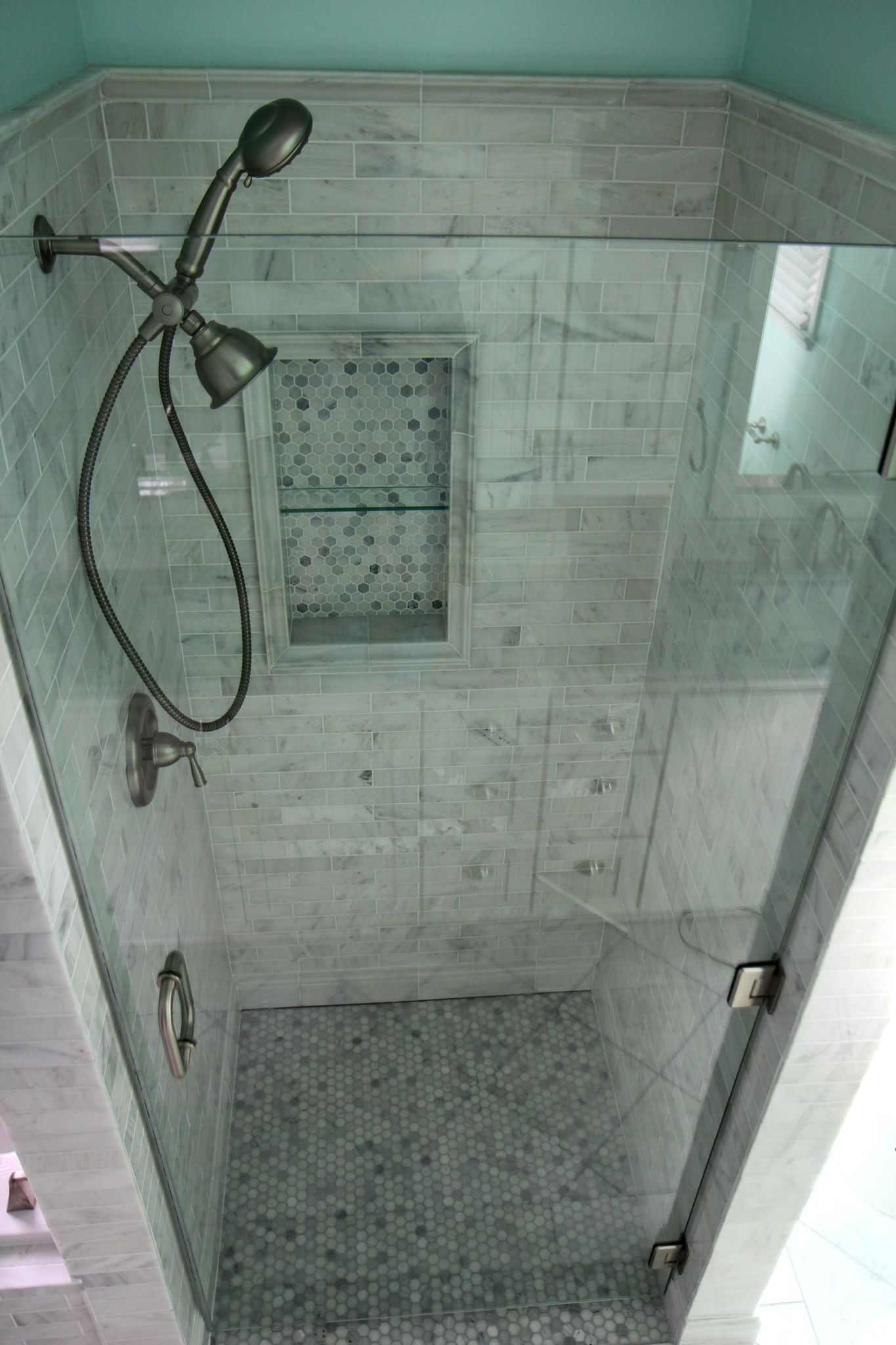 White Carrara marble tile with a frameless glass enclosure ...