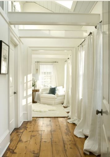 bright white living room and hallway, white curtains, exposed beams