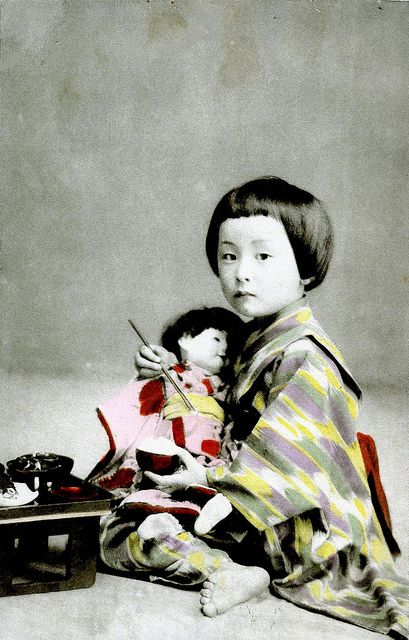 Meal Time 1910 A little Girl feeding her doll some rice.