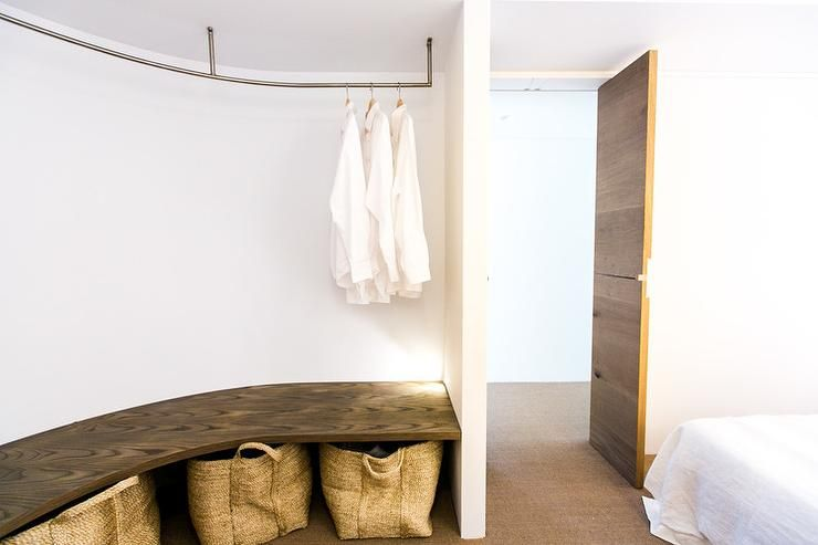 Cottage Bedroom Features Bed Across From An Open Curved Closet Boasting A Curved  Clothes Rail Suspended
